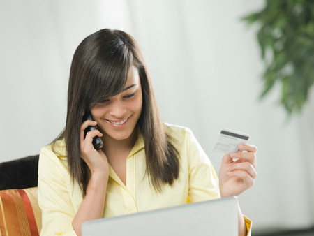 buying time: Young woman using credit card over the phone