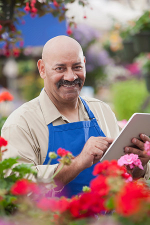 salespeople: Mature man using clipboard in garden centre,portrait LANG_EVOIMAGES