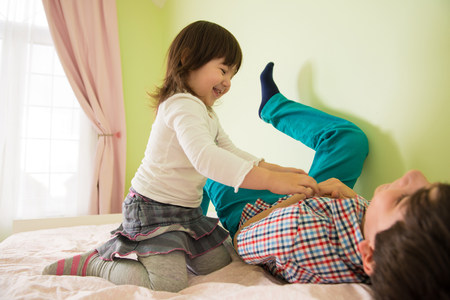 family tickle: Girl tickling brother on bed LANG_EVOIMAGES