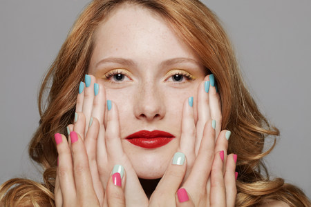 silliness: Young woman with three sets of hands touching her cheeks LANG_EVOIMAGES