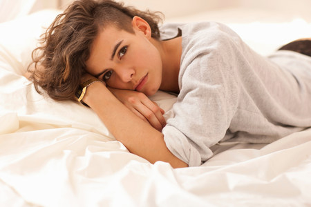 tiredness: Young woman lying on bed,portrait