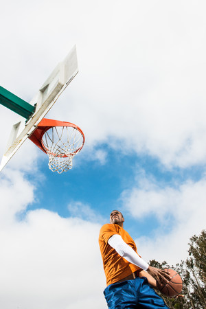 strips away: Young man jumping to score hoop in basketball