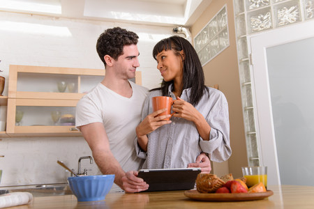 electronic organiser: Young couple with digital tablet in kitchen