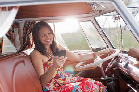 Young woman using mobile phone in camper van LANG_EVOIMAGES