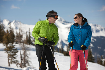 Young woman and mature man in skiwear holding ski poles
