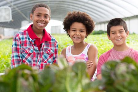 Portrait of three children in plant nursery LANG_EVOIMAGES