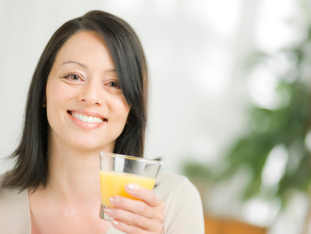 Mature woman holding glass of orange juice,portrait