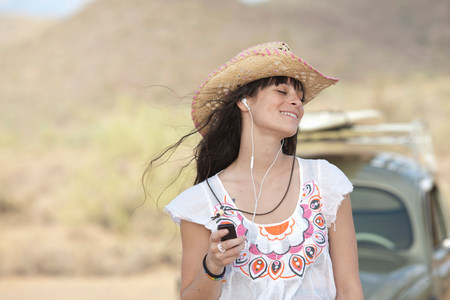 Young woman in cowboy hat wearing earphones,smiling