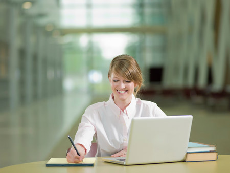 Young student studying taking notes and using laptop,smiling