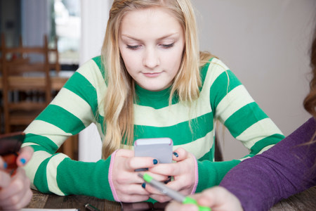 two persons only: Girls sitting at table using smart phone