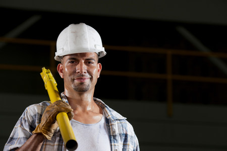 Mid adult construction worker wearing hard hat and holding tool,portrait