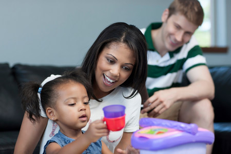 Mid adult woman watching daughter play with toys,smiling
