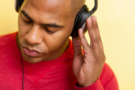Close up portrait of mid adult male eyes closed using headphones LANG_EVOIMAGES