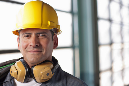 Mature construction worker wearing hard hat and ear defenders,smiling