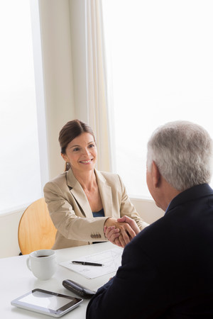 Man and woman shaking hands in meeting