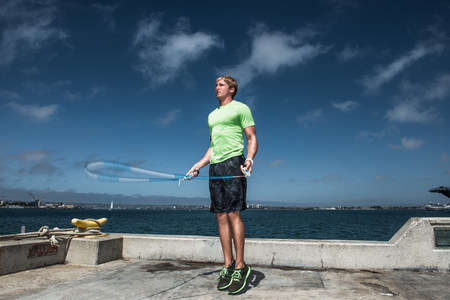 Young man using skipping rope on pier LANG_EVOIMAGES