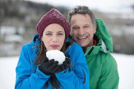 Young woman holding snowball with mature man,portrait