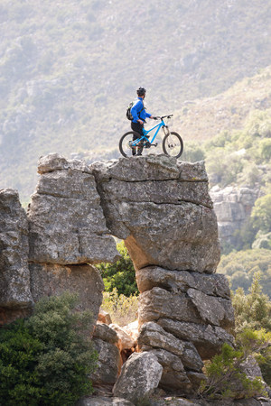 trouble free: Young man standing on rock formation with mountain bike