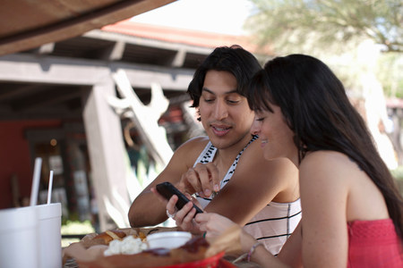 two persons only: Young couple looking at mobile phone in outdoor cafe,smiling