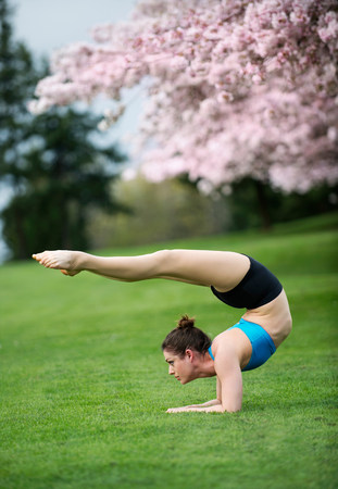 Acrobat performing stretches in park LANG_EVOIMAGES