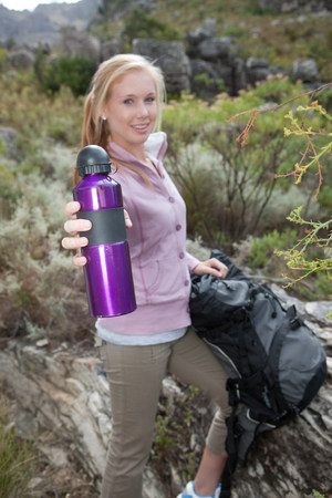 Portrait of young female hiker holding drinks flask