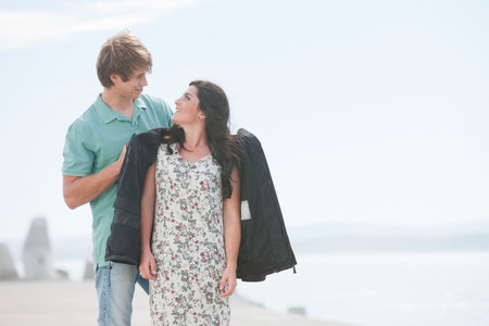 Romantic young couple standing on pier