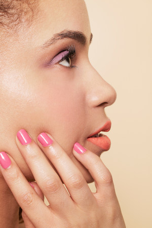 astonishing: Side view of woman wearing make up and nail polish