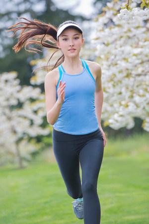 Teenage girl wearing blue sportswear running in park