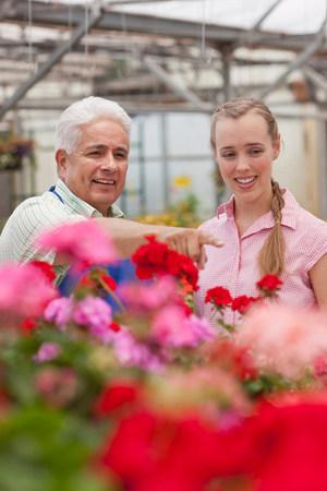 Senior gardener serving mid adult woman in garden centre,smiling