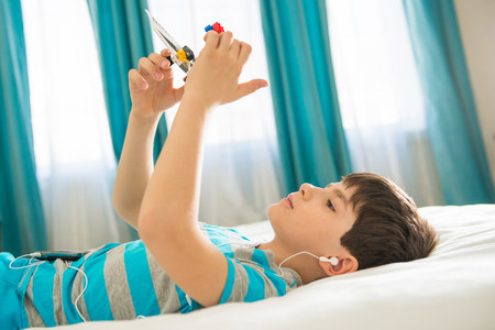 Boy wearing earphones and playing with toy