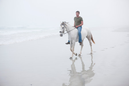 reigns: Man riding horse on beach LANG_EVOIMAGES