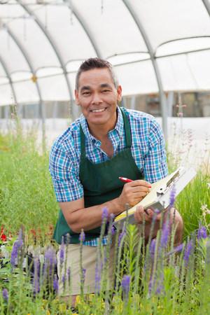 salespeople: Mature man holding clipboard in garden centre,portrait
