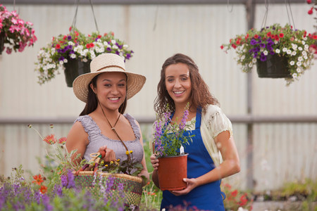 customer facing: Young women holding plants in garden centre,smiling