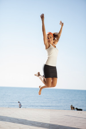 incidental people: Young woman jumping mid air