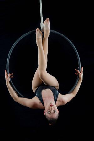 Aerialist performing on hoop in front of black background LANG_EVOIMAGES