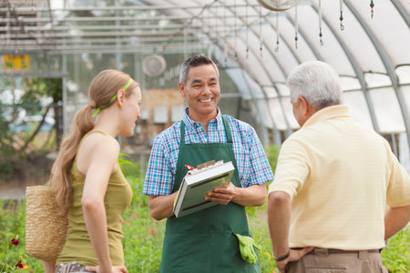 salespeople: Mature sales assistant serving senior man and mid adult woman in garden centre LANG_EVOIMAGES