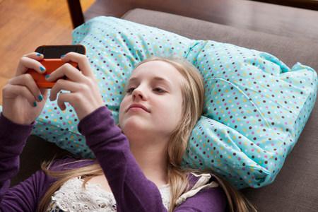Girl lying on sofa playing handheld video game