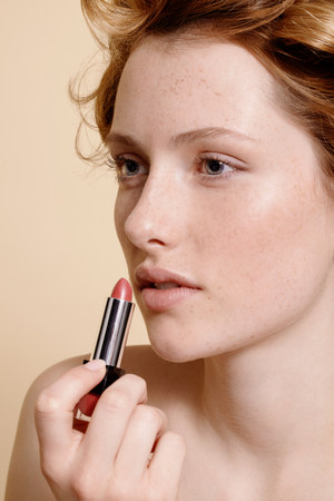half naked: Young woman applying lipstick,close up