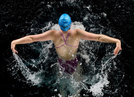exerting: Young woman doing butterfly stroke in swimming pool
