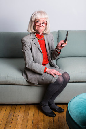 Senior woman sitting on sofa holding mobile phone