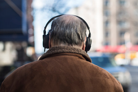 70 75: Rear view of senior man wearing headphones LANG_EVOIMAGES