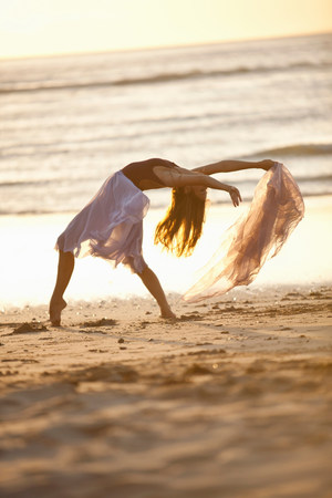 scarves: Young woman dancing on sunlit beach LANG_EVOIMAGES