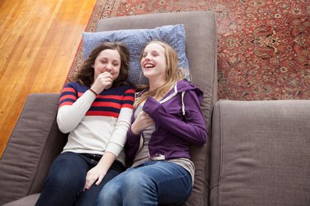 giggling: Girls lying on sofa giggling