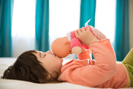 shutting: Girl kissing dolly in bedroom