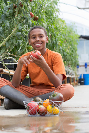 12 13 years: Boy sitting cross legged holding ripe tomato