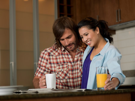 tea breaks: Young woman and mid adult man reading newspaper in kitchen LANG_EVOIMAGES