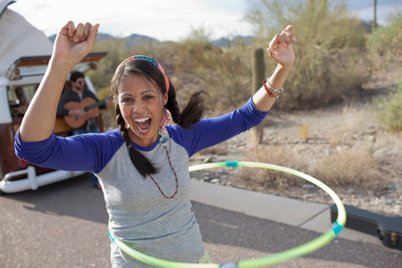 30 years old man: Young woman dancing with plastic hoop on road,portrait LANG_EVOIMAGES