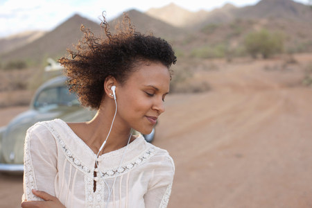 groovy: Young woman wearing earphones in desert on road trip,smiling