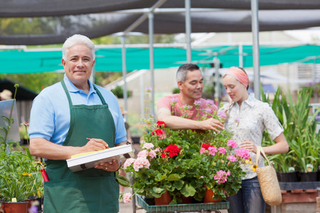 54: Senior gardener using clipboard with customers in background of garden centre LANG_EVOIMAGES