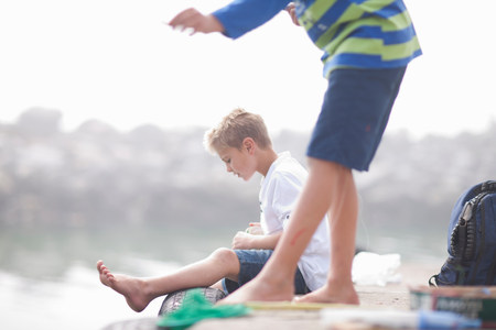 Two young boys fishing on pier LANG_EVOIMAGES